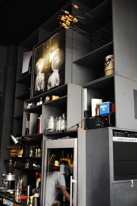 The shelves above the bar display Schmid's collection of art and sculptural pieces created by staff and friends.