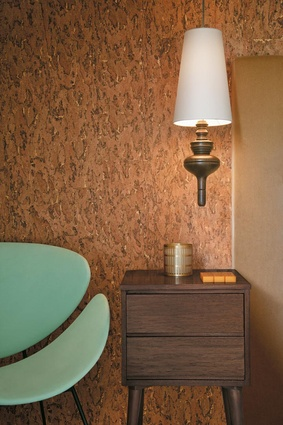 The bedroom is in retro luxe with Burnished Cork wallpaper by Ralph Lauren and a vintage lip chair.