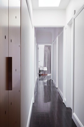 Existing cypress pine floorboards stained black contrast with the white interior surfaces, washed in natural light.