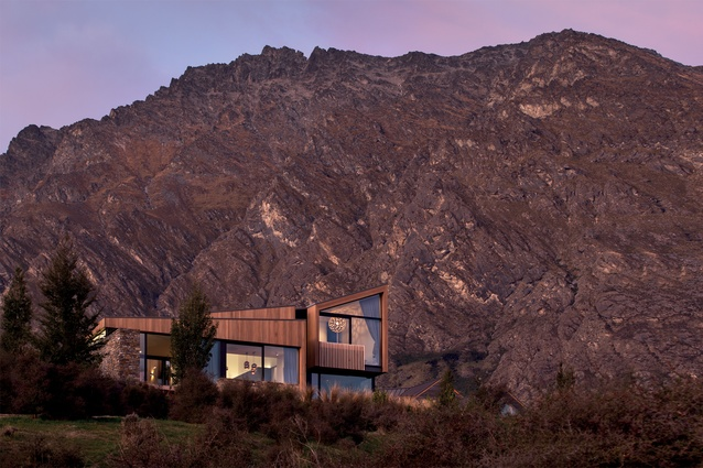 The cedar-clad house is dwarfed by the dramatic mountainous backdrop.