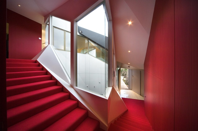 A central courtyard is wrapped by a red stair at the Klein Bottle House.