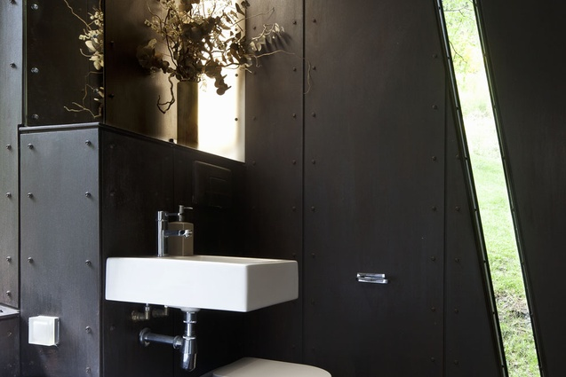 The bathroom has a unique angled window, making a connection to the trees outside.