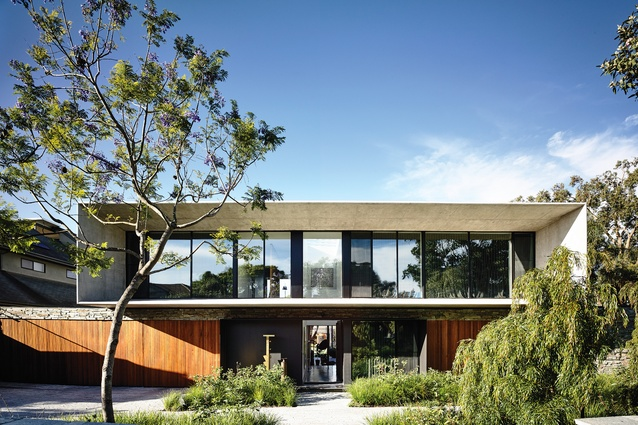 """A large concrete element hovers above an open- plan """"lower"""" building at Concrete House."""
