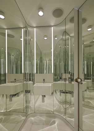 The powder room has green-hued glass curved around each wall, creating a jewel-like mirrored cocoon.