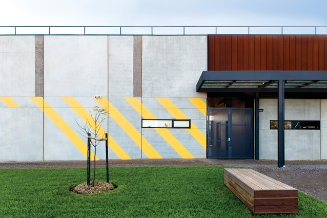 The workshop building is differentiated from the main building by the repeated motif of diagonal yellow stripes along the length of its facade.