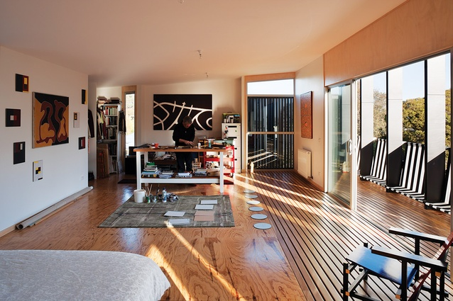 The studio upstairs (also the main bedroom) blurs into the balcony. The black-and-white striped canvas is both balustrade and seating.