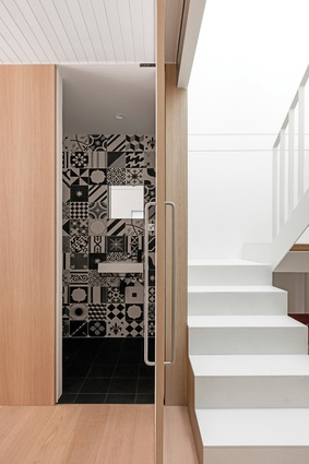 Black-and-white encaustic tiles bring a richness and texture to an otherwise restrained material palette.