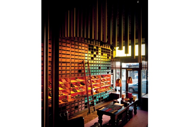 The designer used vertical timber panels to create a cosy atmosphere in the space, which has a tall Victorian ceiling.