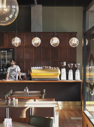 Café co-owner Sam Crofsky. Panelling behind the counter was recycled from a demolished convent.