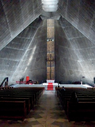 The dim interior of the Church of St Mary, a soaring Catholic cathedral designed by Kenzo Tange in 1964, with its low, heavy hyperbolic ceiling sweeping up above the altar to a concrete crescendo.