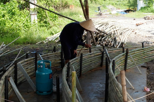 The preparation of the bamboo for construction, traditionally treated for two months in natural waterways followed by a further month's treatment with smoke.