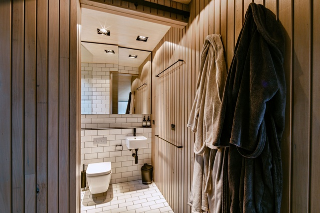 The sharply detailed monochromatic bathroom sits adjacent to the bedroom upstairs.