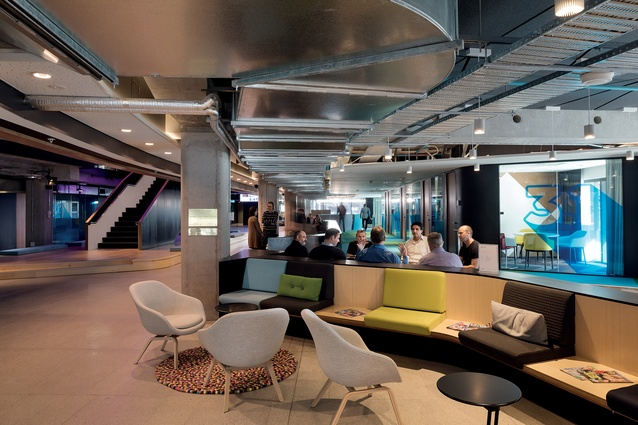 Light, colour, furniture shapes and textures are used to warm and soften the industrial and digital elements here.