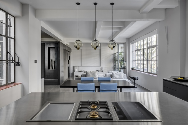 Beneath a triptych of bulbous pendant lights, a sleek monochrome kitchen flows into the open-plan living and dining zone.