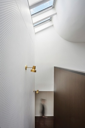 Playful elements are used throughout the home, such as the full-height pegboard wall and pops of brass detailing.