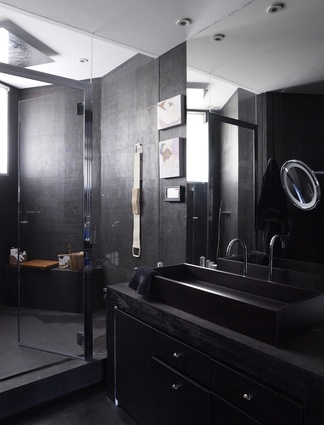 The dark-toned bathroom – in contrast with other rooms – features a custom-made sink and cabinet.