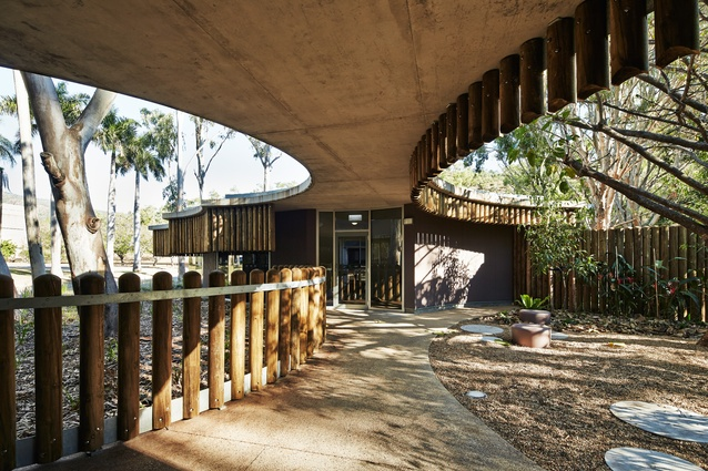 Outdoor play and therapy areas within the site are characterized by the soft curving forms of the canopy roof.