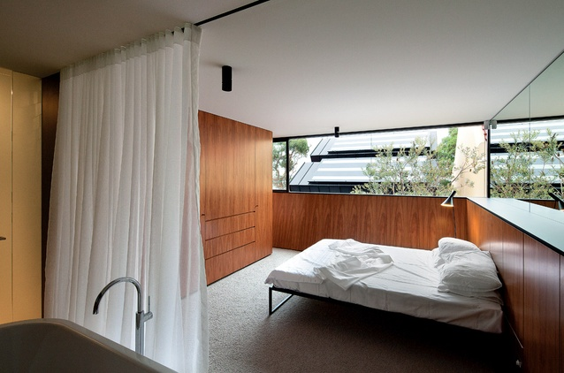"The timber-lined master bedroom with low walls angled out to ""scoop in the sun."""