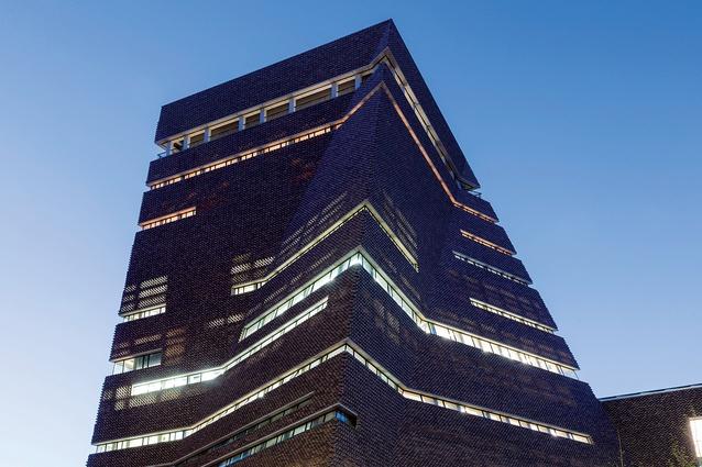 Interior lights glow through the perforated brick lattice at night.