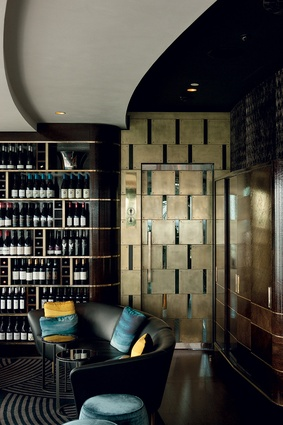 The cocktail seating area and wine storage wall, and the reverse angle, back past low-slung black sofas and, through the chevron motif of the room dividing screens, the first of the dining areas.