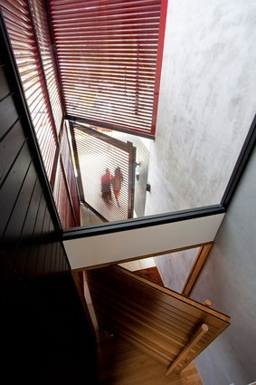 A set of steel screens off the dining room shutter light from the north into a two-storey void space.