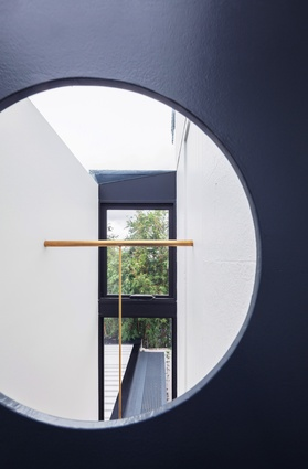 The metal stair that forms a bridge across the void over the entry features a circular peephole.