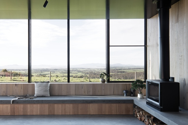 A bench seat lines the perimeter of the living area and the black formply ceiling reflects the colours of the surrounding landscape.