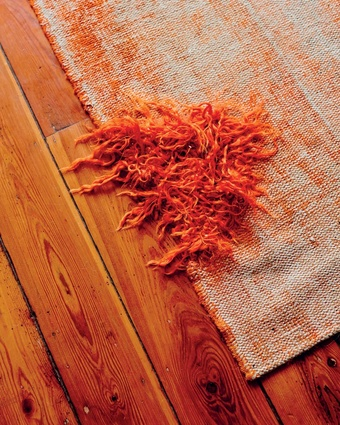 """Vintage rug: """"This is an old, worn-down Turkish rug that has been re-dyed in bright orange. We purchased it like that from a great shop called Loom Rugs""""."""