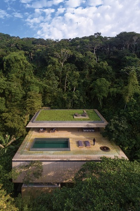 Constructed mostly from concrete and timber, the house features a green roof that blends into the trees when seen from above.