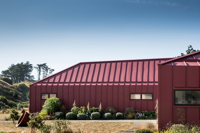 Nohora House, Kapiti Coast, 2012. The form references traditional farm buildings, with their low-pitch hipped roofs. Angled walls wrap around to create shelter on the exposed site.