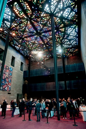 Attendees gather informally under the spectacular stained-glass ceiling in the National Gallery of Victoria's Great Hall, designed by Australian artist Leonard French.