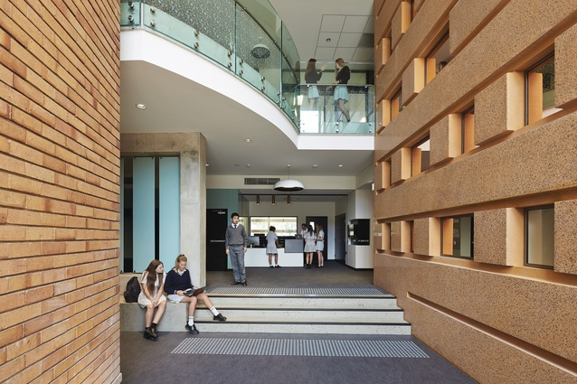The entry to the IT Service area is positioned between the heritage building (left) and the New Learning Centre's polished precast concrete forms. The concrete wall wraps from the outside in and features the school's motto in morse code, creating recessed windows and mirrors.