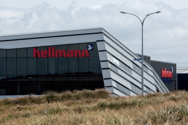 On the way to and from Auckland Airport, the Hellmann Worldwide Logistics building reveals itself among the sharply landscaped mounds of gravel and planting.