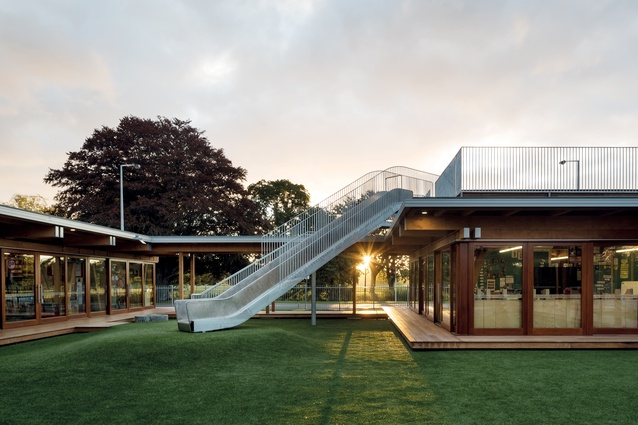 A rooftop playground provides pupils of Cathedral Grammar School with a slide down to a grass-laid courtyard below, in the middle of a new timber building.