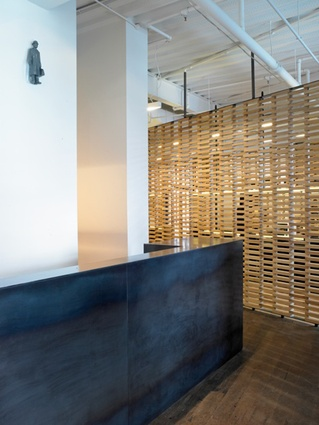 A large, steel reception desk is finished in black wax.