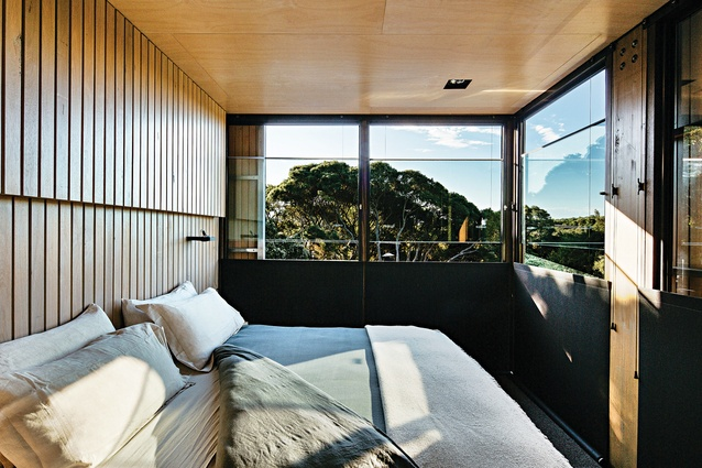 The loft bedroom floats above the living area and enjoys a leafy outlook.