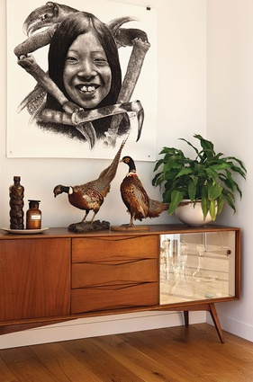 A charcoal drawing from Liam Gerrard hangs above a mid-century unit.