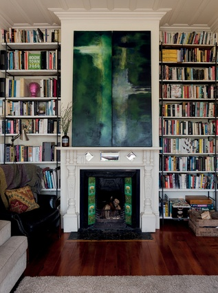 "Bookshelves. ""This is perhaps one area where Charles doesn't mind clutter. The shelves were made by Stephen Brookbanks and the paintings on the mantelpiece are by Charles."""