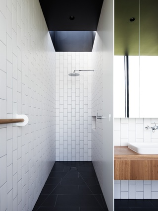 The bathroom features custom joinery and fittings and a skylight above the shower for extra natural light.