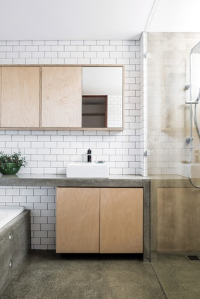 The bathroom is an exercise in craftsmanship and detail, with white tile and concrete offset by birch ply joinery.