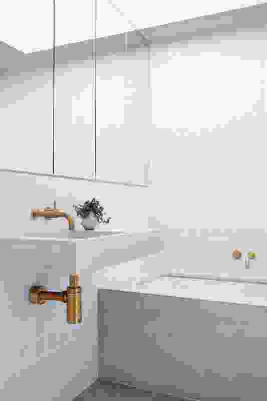 黄铜龙头为明快明亮的浴室增添了温暖,也以哑光白色瓷砖和混凝土梳妆台为特色。
