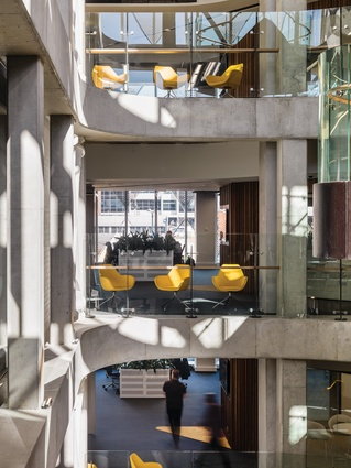 The building's design aesthetic is basic and raw, with exposed concrete the defining material in the central atrium.