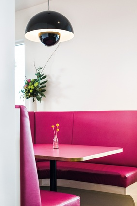 A custom-made hot pink circular booth creates a warm sanctuary in the middle of the front dining area.