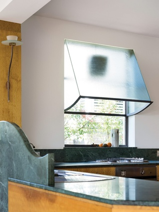 "A ""rangehood"" was inventively created from a simple window fan and an elegant wired glass awning."