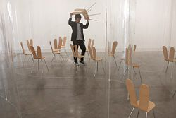 """Nishizawa arranging the """"Rabbit chairs"""" (designed by the architects) for the installation."""