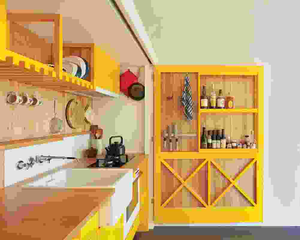 """A large hinged door doubles as a pantry in a kitchen that """"opens up, hides away, slides along and folds out."""""""