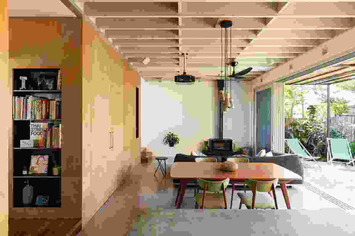 A money-saving strategy to expose structural beams provides depth and rhythm to the room.
