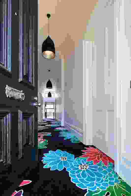 A flower-cloud-carpeted corridor leads from the entry to the red box of the kitchen.