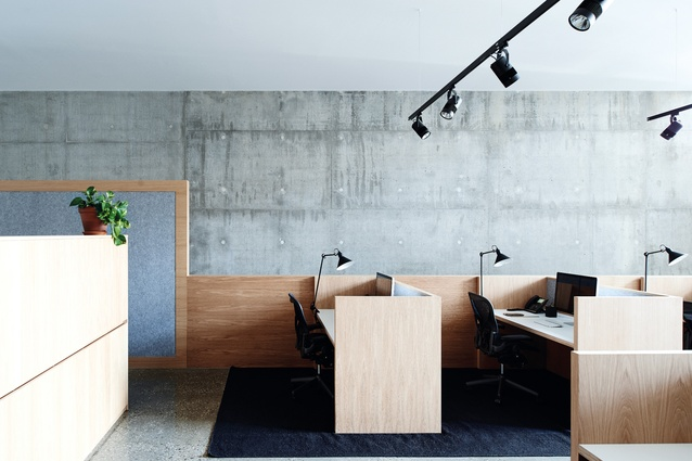 Each workstation is wrapped in a timber surround, lined with felted acoustic panelling, which acts as a soft counter material to the concrete.