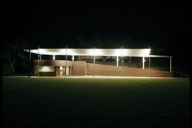 A lightweight steel roof is tethered above the brick pavilion, its underside emphasized by uplighting.